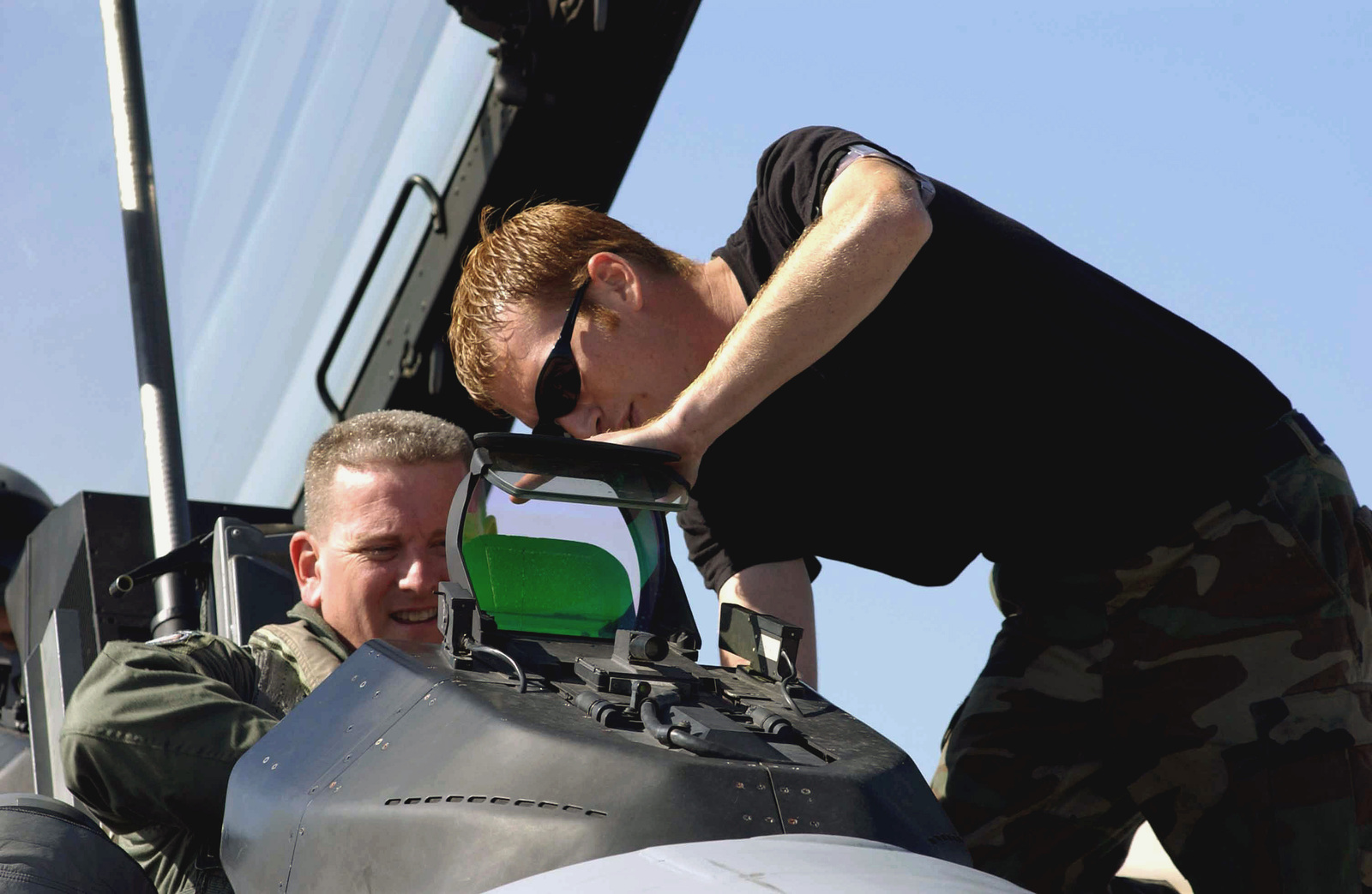 US Air Force (USAF) Lieutenant Colonel (LTC) Mark Moore (left), Commander, 555th Fighter Squadron (FS), gets help from his Crew CHIEF, USAF STAFF Sergeant (SSGT) Amos Olson, 31st Aircraft Maintenance Squadron (AMXS), 31st Fighter Wing (FW), as he straps into the cockpit of his USAF F-16 Fighting Falcon aircraft, while deployed at Decimomannu Air Base (AB), Sardinia, Italy