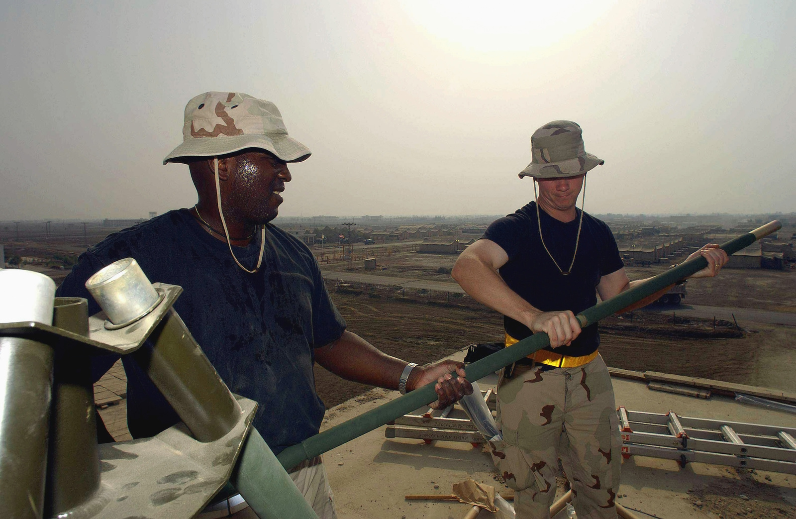 US Air Force (USAF) STAFF Sergeant (SSGT) Russ Smith (left) and USAF SSGT Keith Durant, both Ground Radio Maintenance Technicians assigned with the 438th Expeditionary Communications Flight (ECF), work to install a GRA-4 Motorola Antenna mast while deployed at a forward location in support of Operation ENDURING FREEDOM