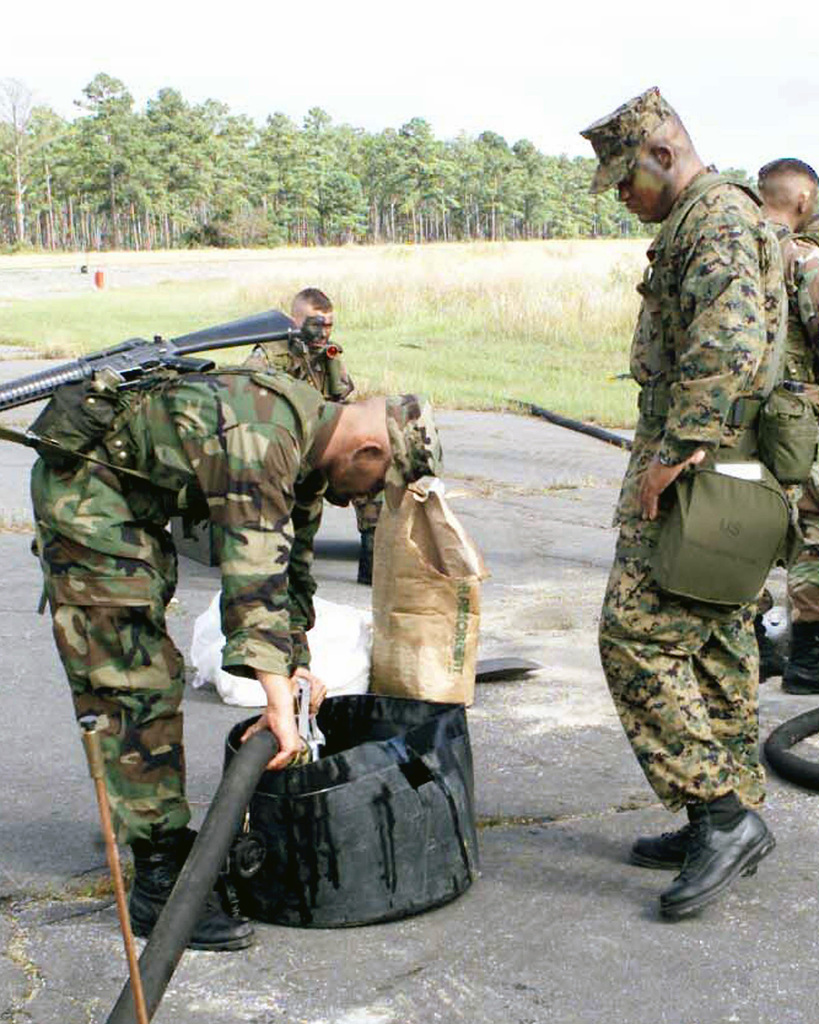 US Marine Corps (USMC) Private First Class (PFC) Fowler (left), slings his 5.56 mm M16A2 rifle, as he uses a vacuum hose to remove excess fuel from a collection pan, as USMC GUNNERY Sergeant (GYSGT) Wright looks on. Both Marines are assigned to Marine Wing Support Squadron Two Seven Four (MWSS-274), Air Operations Refueling, and are participating in a field refueling exercise at Oak Grove Field, located at Marine Corps Air Station (MCAS) Cherry Point, North Carolina (NC)