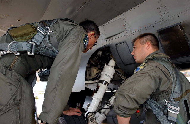 """Deployed to Sardinia, US Air Force (USAF) Brigadier General (BGEN) Mike Worden, the 31st Fighter Wing (FW) Commander and Captain (CAPT) Mathew """"Saigon"""" Higgins, a pilot with the 510th Fighter Squadron (FS), discuss the condition of the main gear prior to their flight"""