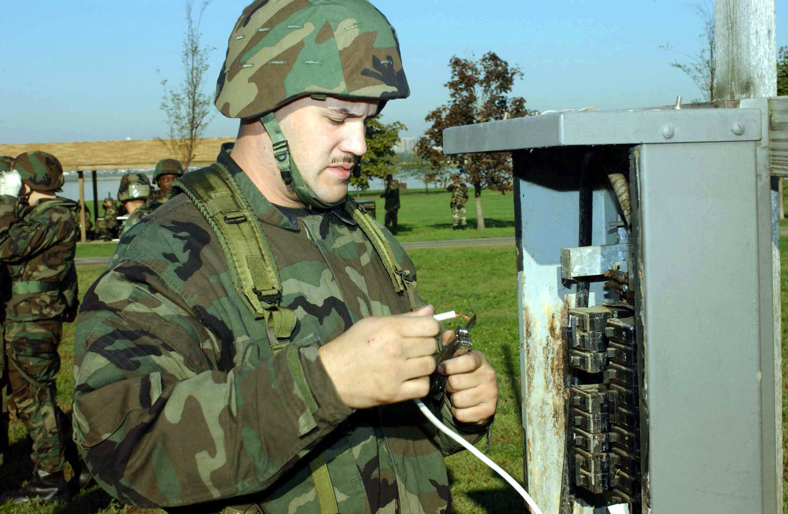 US Air Force (USAF) STAFF Sergeant (SSGT) Ford of the 11th Civil Engineering Squadron (CES) splices wire in a circuit breaker box during Exercise SABERTOOTH 2002, at Gieseboro park
