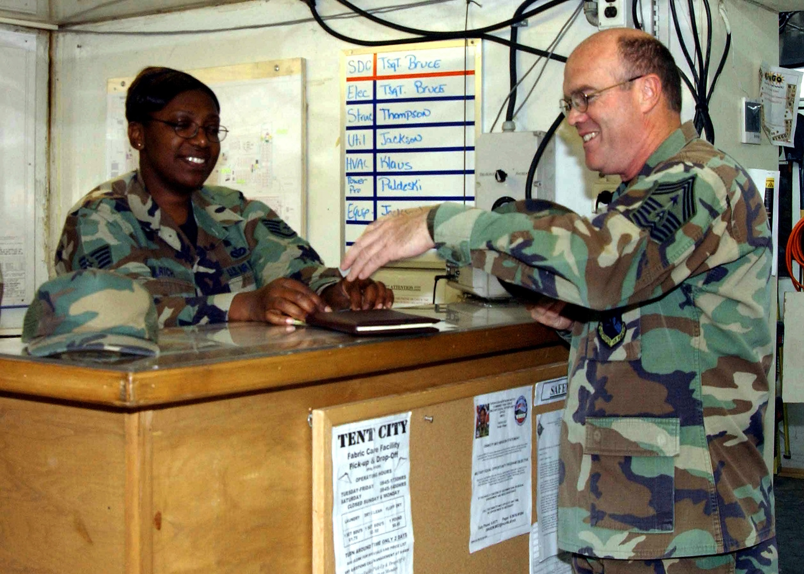 US Air Force (USAF) STAFF Sergeant (SSGT) Tracy Ulrich (left), Exercise Prime Beef, Customer Service Representative, greets USAF CHIEF MASTER Sergeant (CMSGT) Henry Leopard, First Sergeant, Combined Task Force, inside the deployed civil engineering compound tent at Incirlik Air Base (AB), Turkey, during Operation NORTHERN WATCH