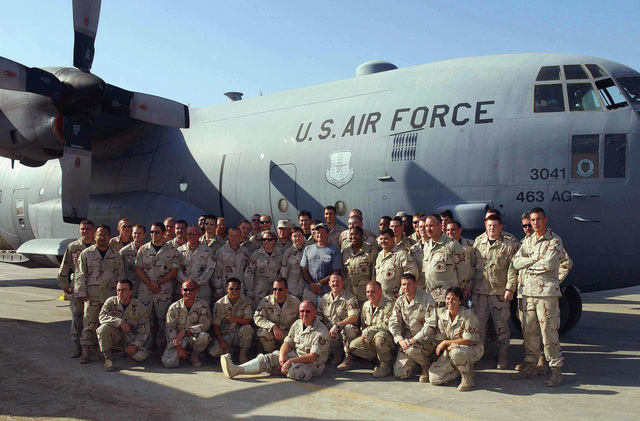 Actor and comedian Robin Williams, standing center, poses with members assigned to the US Air Force (USAF) 776th Expeditionary Airlift Squadron (EAS), next to a C-130 Hercules aircraft during a visit to a forward deployed location (FDL) in support of Operation ENDURING FREEDOM