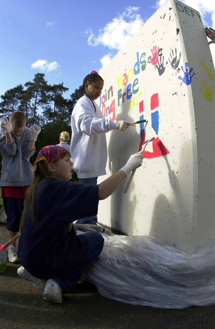 Tia Wilcox, right and Caitlin Noll, both 10 years of age, paint a concrete barricade with a drug free message from the Drug Education For Youth (D.E.F.Y.) programs at Ramstein Air Base (AB), Germany