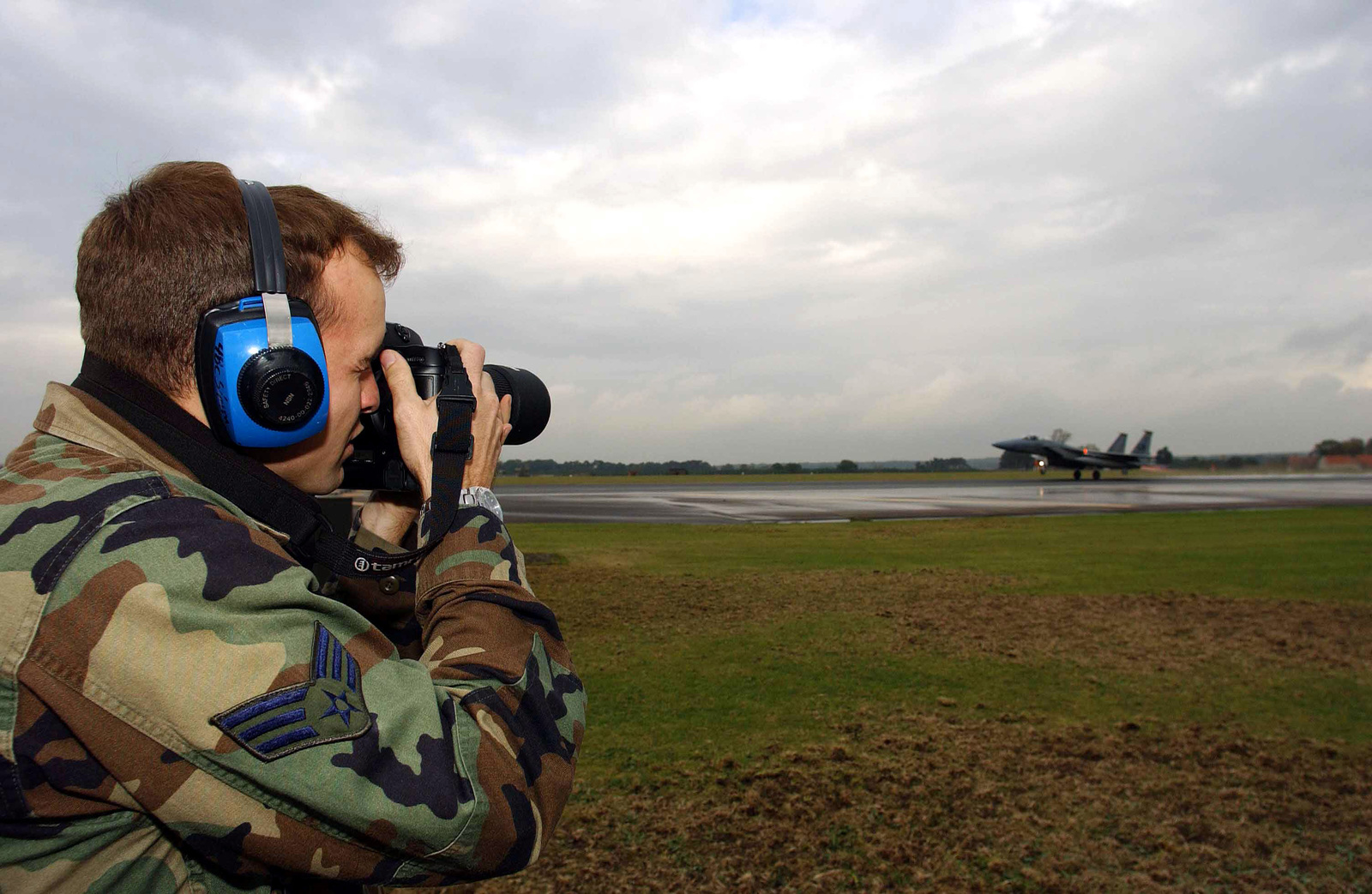 US Air Force (USAF) SENIOR AIRMAN (SRA) James Harper, a 48th Communications Squadron (CS) photographer, assigned to Royal Air Force (RAF) Lakenheath, England, documents flight operations on the runway as a 493rd Fighter Squadron (FS) F-15C Eagle takes off