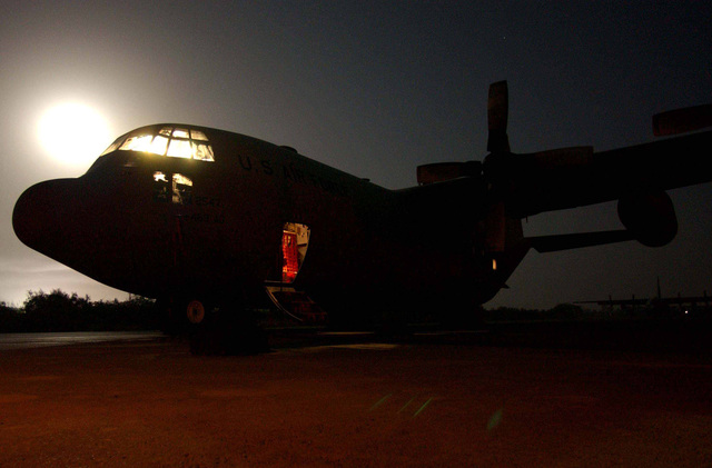 A moonlit US Air Force (USAF) C-130 Hercules sits on the parking ramp at a forward deployed location while 776th Expeditionary Airlift Squadron (EAS) in support of Operation ENDURING FREEDOM