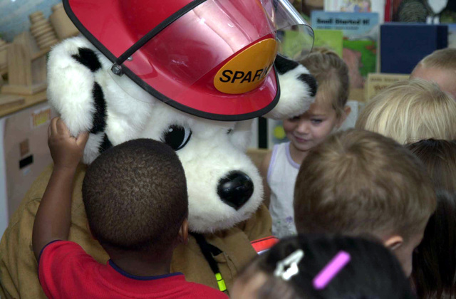Sparky the Fire Dog greets kids at the Shima No Ko child development center, showing them what to do in case of a fire emergency