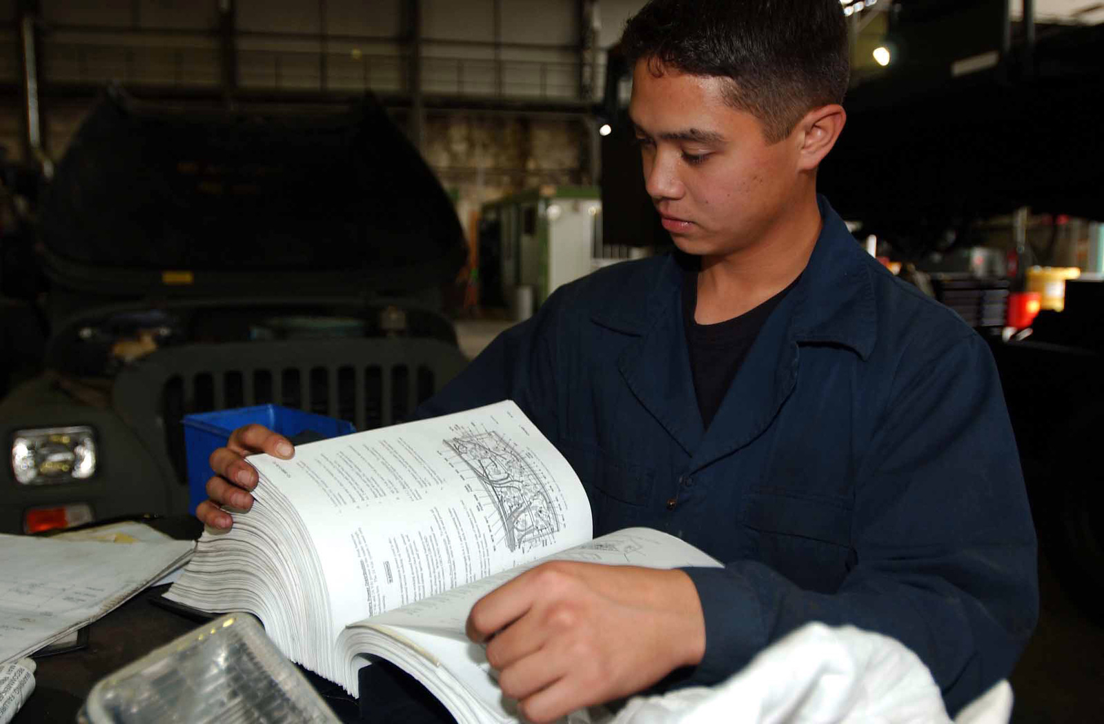 US Air Force (USAF) AIRMAN First Class (A1C) Charles Pichelmeyer, a Special Purpose Vehicle & Equipment Maintenance Apprentice, with the 31st Logistics Readiness Squadron (LRS), reads the Operator Maintenance Instructions prior to performing maintenance on a transportation vehicle