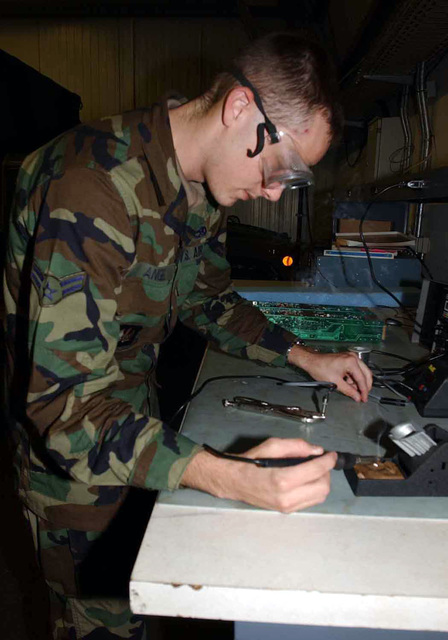 US Air Force (USAF) AIRMAN First Class (A1C) Patrick S. Angel, with the 606th Air Control Squadron (ACS), solders an analog test set adapter, in order to test communication lines at Spangdahlem Air Base (AB), Germany