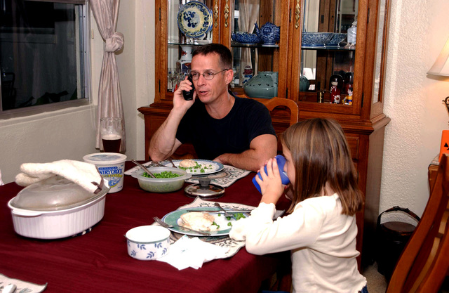 "US Air Force (USAF) Lieutenant Colonel (LTC) Edward Keegan, Commander, 18th Communications Squadron (CS) attempts to enjoy a sit down dinner with daughter Ashton, inside his quarters at Kadena Air Base (AB), Japan. LTC Keegan is being photographed for the ""Day in the Life of the Armed Forces"" project, which is a joint venture between the Department of Defense (DOD) and the Epicenter Communications Company"