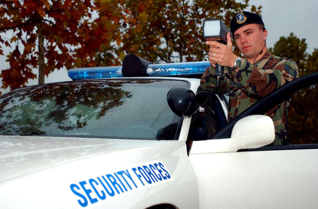 US Air Force (USAF) Security Forces member, STAFF Sergeant (SSGT) Dominic Vecchi, creates a barricade using a vehicle and measures speeders using a dashboard detachable radar detector on the flight line perimeter road