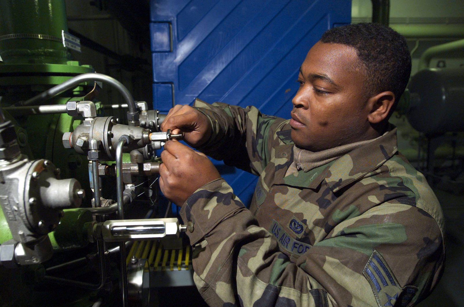 US Air Force (USAF) SENIOR AIRMAN (SRA) Jerome Stevenson, with the 52nd Civil Engineering Squadron (CES), with a liquid fuels maintenance unit, adjusts the rate of flow on a valve, at Spangdahlem Air Base (AB), Germany