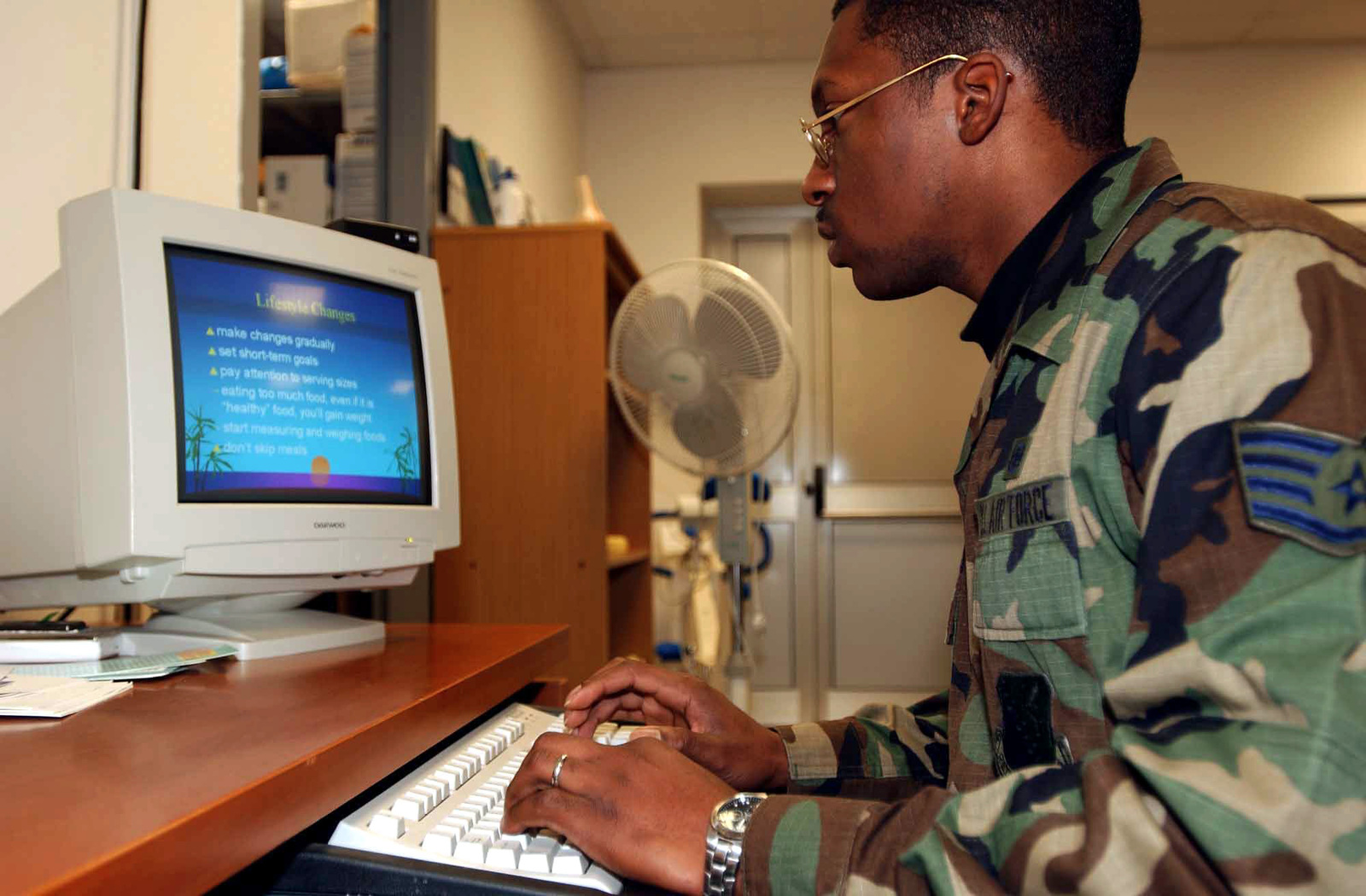 """US Air Force (USAF) STAFF Sergeant (SSGT) Joseph Orimoloye, a Diet Therapy Technician, with the 31st Medical Group (MG), Health and Wellness Center (HWC), prepares a PowerPoint briefing titled """"Weight to Go"""" that teaches military members about balanced meals"""