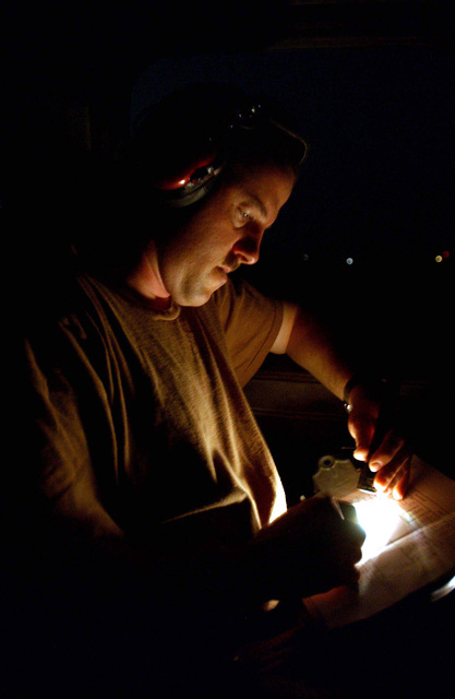 US Air Force (USAF) Technical Sergeant (TSGT) Jonathan Boyd, a maintainer with the 776th Expeditionary Airlift Squadron (EAS), fills out a checklist before allowing a C-130 Hercules aircraft to take off on a mission to a forward-deployed location (FDL) in support of Operation ENDURING FREEDOM