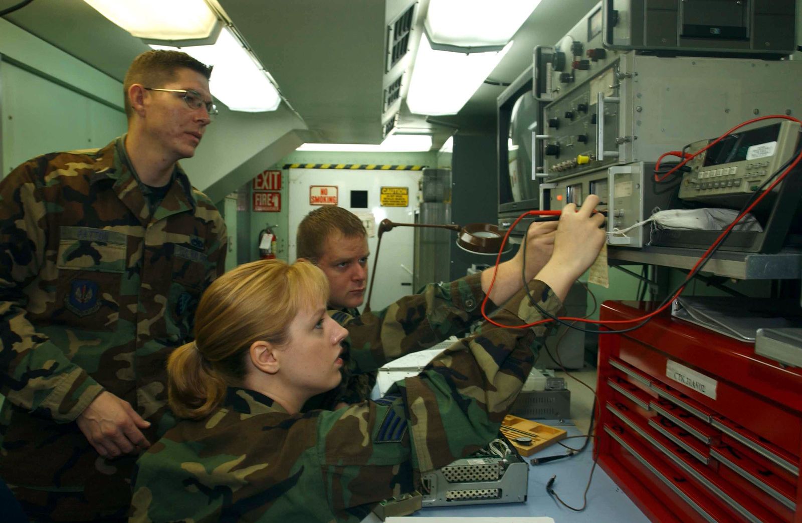 While US Air Force (USAF) STAFF Sergeant (SSGT) Jason Patton looks on, SENIOR AIRMAN (SRA) Jennifer Dear and SENIOR AIRMAN (SRA) John Mackstroth, Avionic Sensor Technicians and members of the 31st Maintenance Squadron (MS) try to stabilize power fluctuations as they perform scheduled maintenance on an Improved Airborne Tape Recorder (EVO-520 IATR)