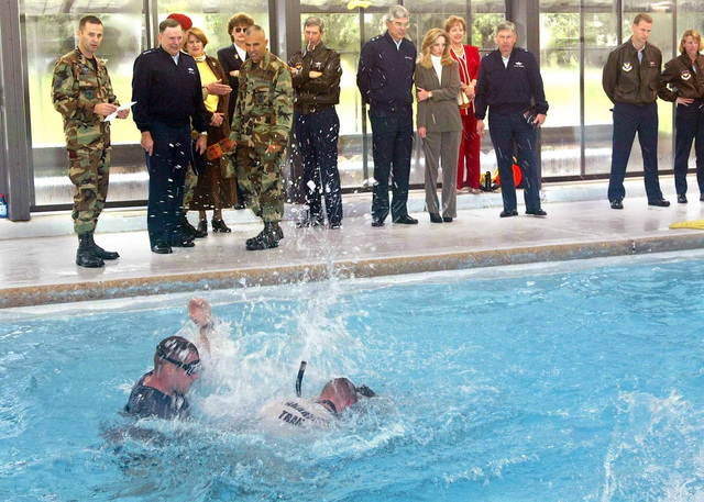 On a tour of Lackland Air Force Base (AFB), Texas, United States Air Force (USAF), CHIEF of STAFF (CS), General (GEN) John P. Jumper, second from left, watches a water survival demonstration by a 342nd Training Squadron (TS) pararescue trainee. With the CS are left to right, MASTER Sergeant (MSGT) Bryan Winder, a Combat Training Flight Superintendent, Major (MAJ) Michael P. Buonaugurio, the 342nd TS Commander, GEN Donald G. Cook, the Air Education and Training Command (AETC) Commander, Major General (MGEN) John F. Regni, the 2nd Air Force Commander and Brigadier General (BGEN) Fred D. Van Valkenburg, Commander, 37th Training Wing (TW). Accompanying the tour are Mrs. Ellen Jumper, Mrs....