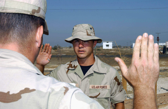 An unidentified US Air Force (USAF) Officer (foreground) administer the Oath of Reenlistment to USAF SENIOR AIRMAN (SRA) Dave Cantwell, Contract Escort, 438th Expeditionary Civil Engineering Flight, while deployed at a forward location in support of Operation ENDURING FREEDOM