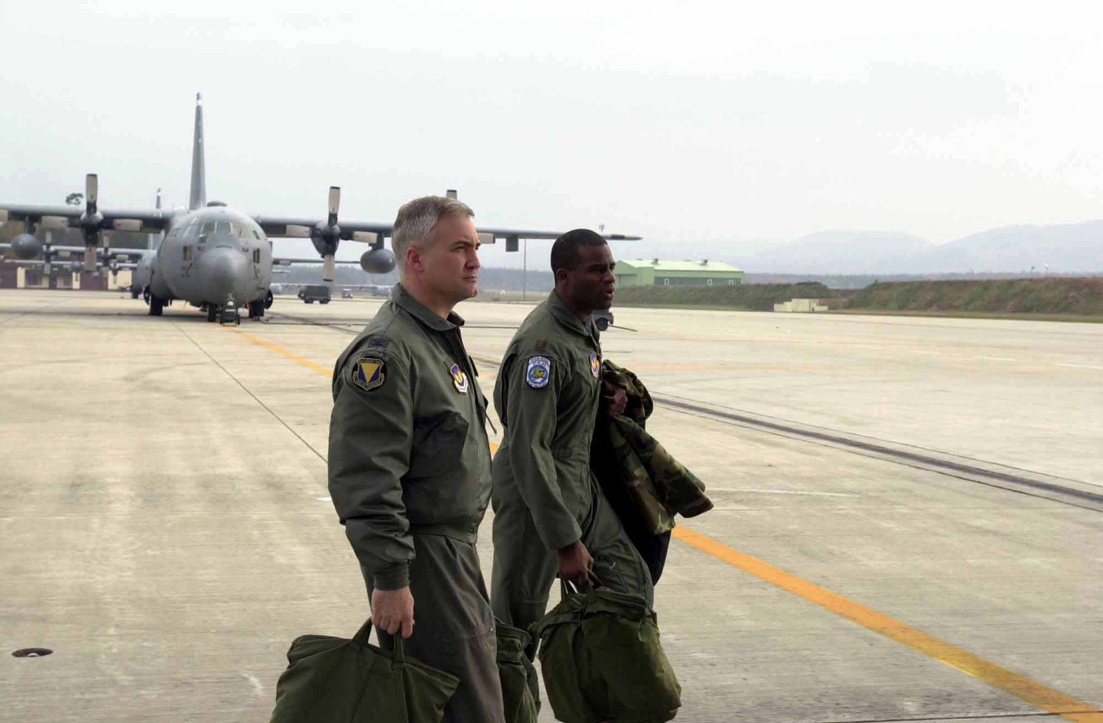 US Air Force (USAF) Colonel (COL) Erwin F. Lessel III (foregound), Commander, 86th Airlift Wing (AW) and USAF Major (MAJ) Brian Hill, a C-130 Hercules aircraft Pilot from the 37th Airlift Squadron (AS), walk across the flight line as they prepare for a mission from Ramstein Air Base (AB), Germany