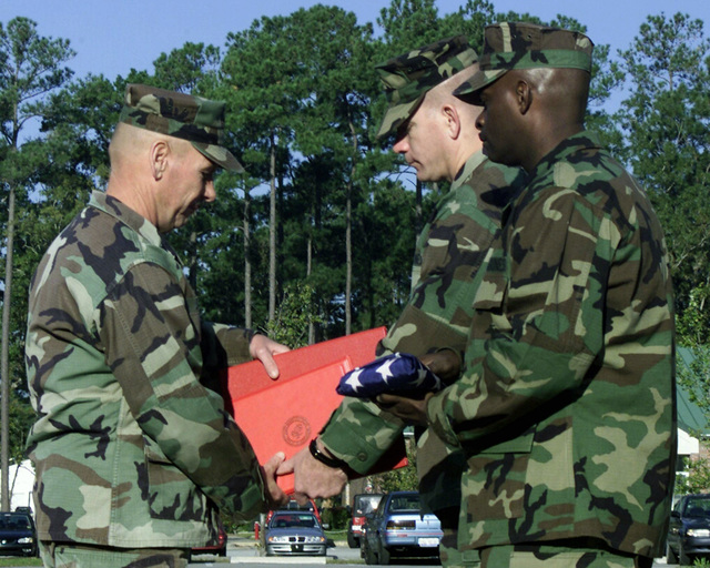 US Marine Corps (USMC) MASTER GUNNERY Sergeant (MGYSGT) Anthony P. Silva (left), assigned to Marine Wing Support Squadron Two Seven One (MWSS-271), receives the Colors and Awards from USMC Lieutenant Colonel (LTC) Alan L. Thoma (background right) and Sergeant Major (SGM) Robert E. Roberts Jr. during his Retirement Ceremony held at Marine Corps Air Station (MCAS) Cherry Point, North Carolina (NC)