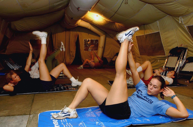 US Air Force (USAF) AIRMAN First Class (A1C) Tiffany Johnson (foreground), Fitness SPECIALIST, 438th Expeditionary Services Flight (ESF), instructs an aerobics class inside a base gym at an undisclosed forward location during Operation ENDURING FREEDOM