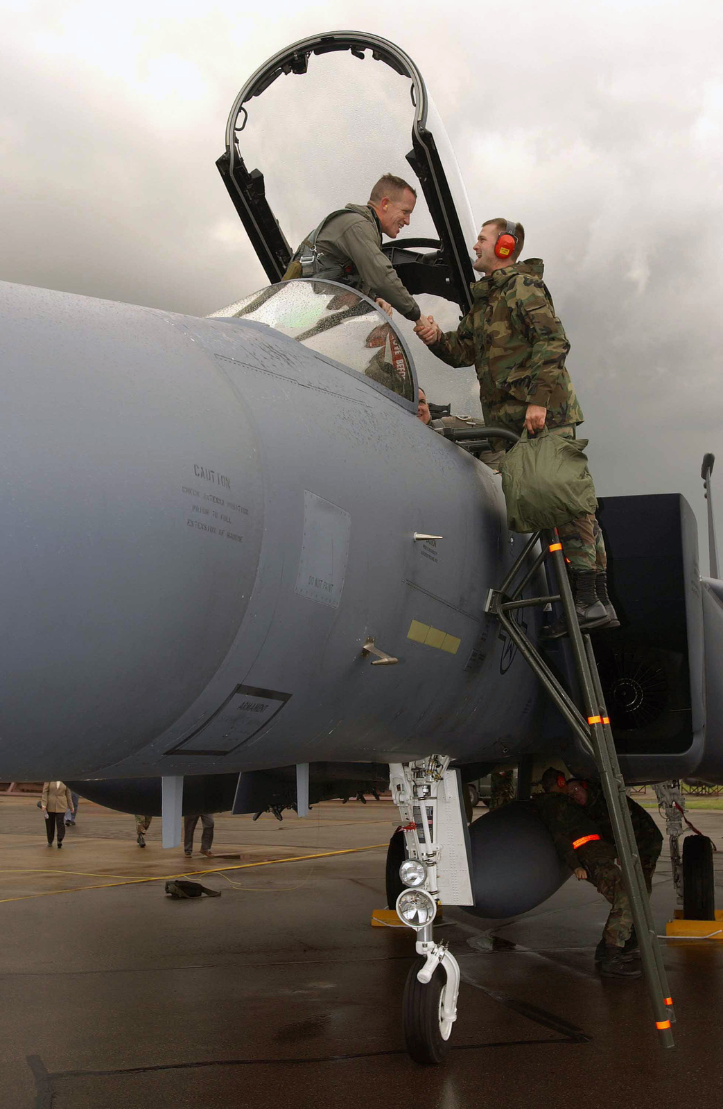US Air Force (USAF) Lieutenant Colonel (LTC) Kent Laughbaum (left), Commander, 494th Fighter Squadron (FS), is assisted by an unidentified Crew CHIEF from the 48th Aircraft Maintenance Squadron (AMXS), 48th Fighter Wing (FW), as he exits a USAF F-15E Strike Eagle aircraft, on the flight line at Royal Air Force (RAF) Lakenheath, United Kingdom (UK). Two new Strike Eagle aircraft were flown over by 494th FS aircrews and will be assigned to the unit