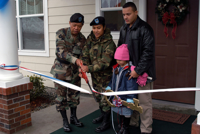 Lieutenant General (LGEN) Edward Soriano (left), USA, Commander, I Corps and Fort Lewis, and Sergeant (SGT) Randy Lock, USA, cut the ceremonial ribbon dedicating a new housing area under the Residential Community Initiative (RCI). SGT Locks husband and daughter look on during the Ribbon Cutting Ceremony. RCI is a program to privatize Army housing and provide better housing for soldiers and their families and reducing the cost to the taxpayer