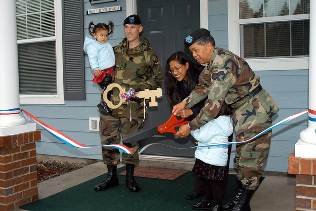 Lieutenant General (LGEN) Edward Soriano (right), USA, Commander, I Corps and Fort Lewis, and Michelle Forgery cuts the ceremonial ribbon as her husband STAFF Sergeant (SSG) Jason Forgery, USA, holding their daughter, looks on during the Ribbon Cutting Ceremony dedicating a new housing area under the Residential Community Initiative. RCI is a program to privatize Army housing and provide better housing for soldiers and their families and reducing the cost to the taxpayer