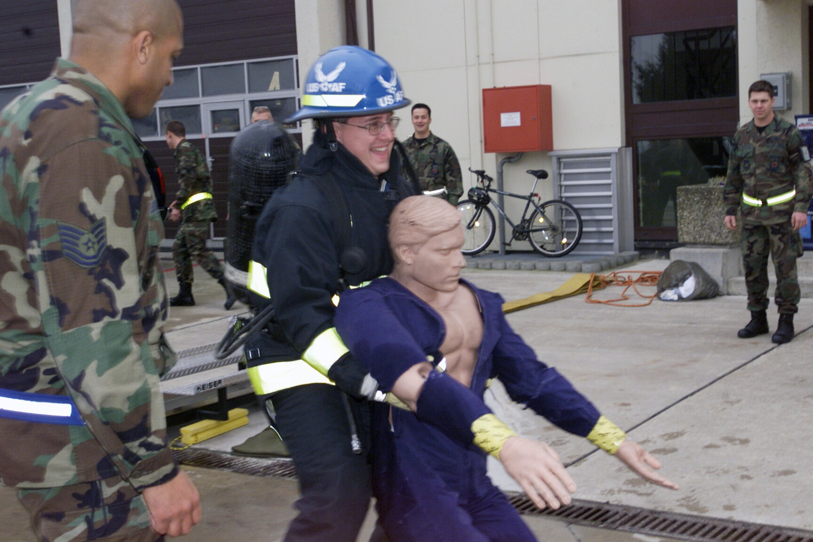 US Air Force (USAF) Technical Sergeant (TSGT) George Deshields, 52nd Civil Engineering Squadron (CES), watches as Restless Heart band member David Innis, in full fire suit, drags a practice dummy during a firefighter exercise at Spangdahlem Air Base (AB), Germany. Country music group Restless Heart and The Jamie O'Neal Band are top performers in this years Operations Seasoning's Greetings concert at the base