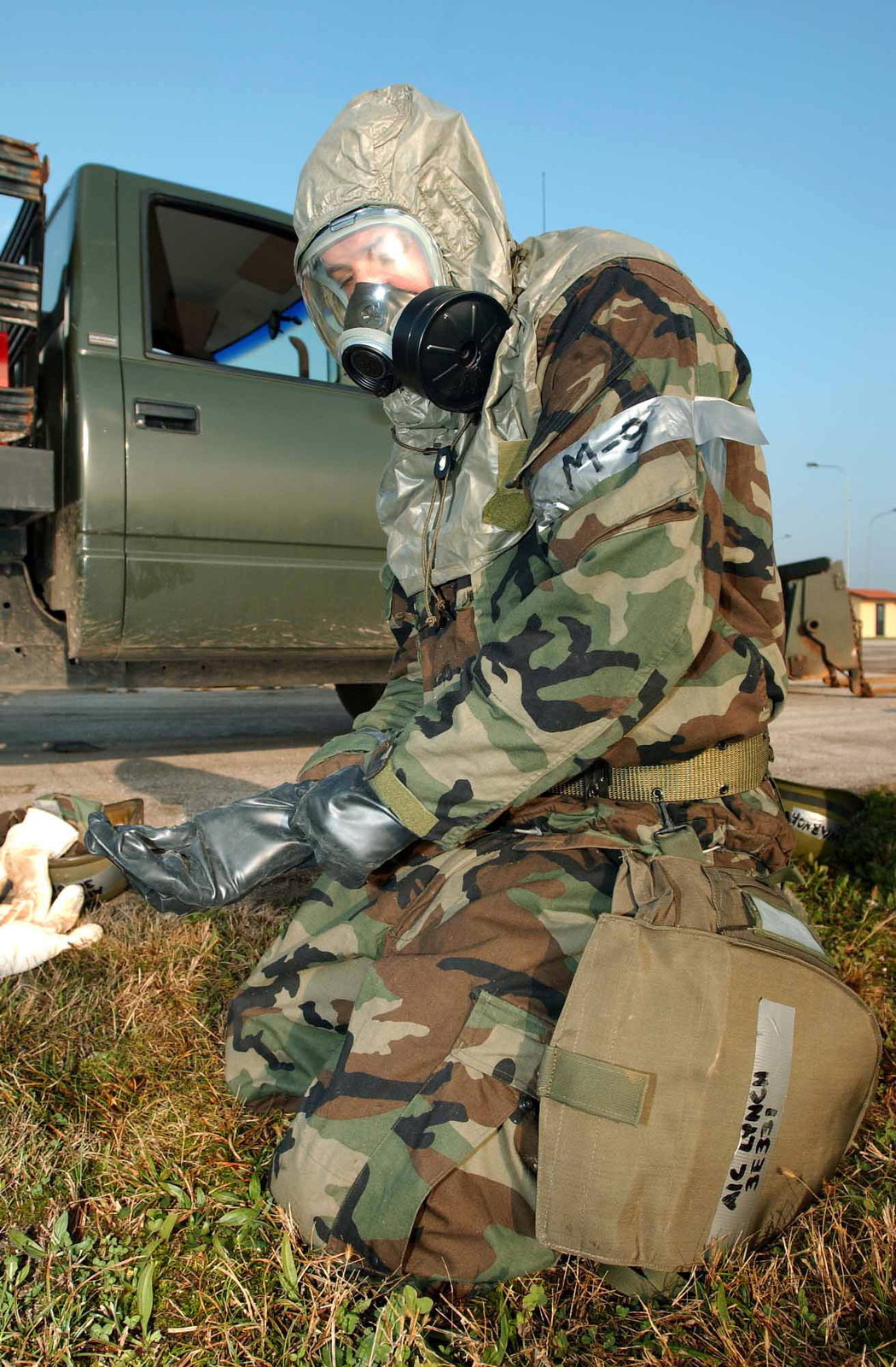 Completing his Mission-Oriented Protective Posture response level 4 (MOPP-4) suit, US Air Force (USAF) AIRMAN First Class (A1C) Chad R. Lynch, 31st Civil Engineer Squadron (CES), Rapid Runway Response (RRR) team member dons his rubber gloves during a simulated chemical attack. The attack used to hone the skills of the 31st CES Triple-R in event of an attack as they train for the upcoming NATO Tactical Evaluation