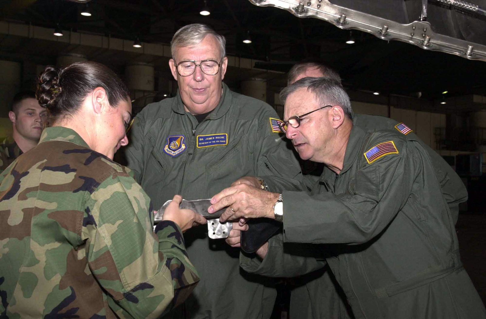 US Air Force (USAF) Captain (CAPT) Diana Stuart (left), Maintenance Supervisor, 18th Equipment Maintenance Squadron (EMS), shows Dr. James G. Roche (center), Secretary of the Air Force, and USAF Major General (MGEN) Mark V. Rosenker, Mobility Assistant to the Director, the severe corrosive effects of saltwater and the environment have on aircraft and ground equipment at Kadena Air Base (AB), Japan