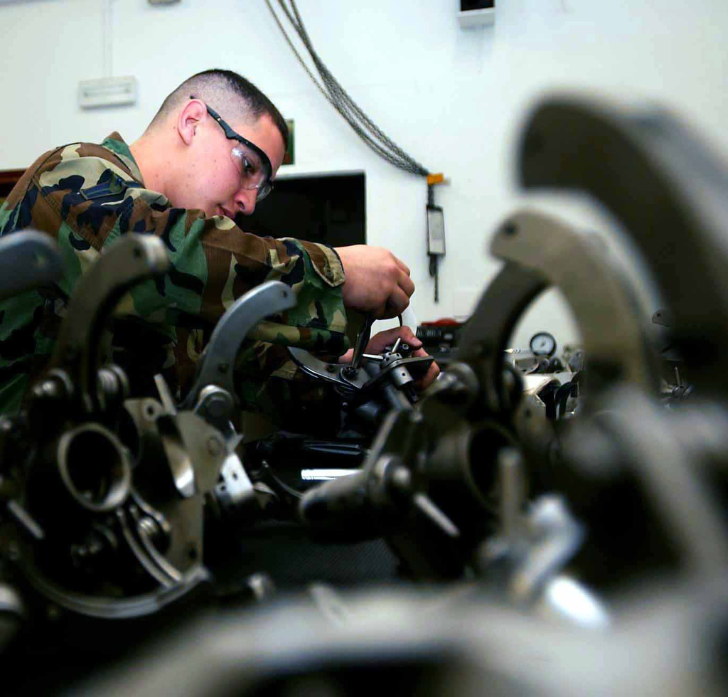 US Air Force (USAF) AIRMAN First Class (A1C) Carlos Ramos, Aircraft Armament Systems Apprentice, disassembles a Suspension Utility Unit-20 (SUU-20) Multiple Ejector Rack Assembly to look for corrosion, dirt, and foreign objects that could affect its performance