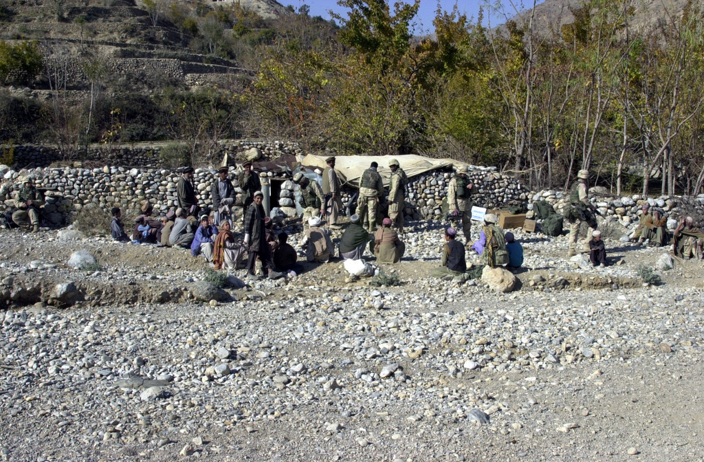 Local Afghani resident from the village of Lowa, gather to receive free medical aid and basic humanitarian assistance, as US Army (USA) Soldier visit their village during a damage claim investigation patrol in the Kohi Sofi District of Afghanistan, during Operation ENDURING FREEDOM