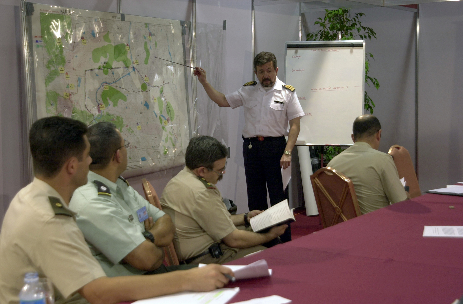Argentine Republic Navy Captain (CPT) Juan Carlos Diez (standing background), uses a map to brief Joint Task Force Commanders during the Mid-Planning Conference for Peacekeeping Operations South 03 (PKO South 03), held at the Sheraton Hotel, Buenos Aires, Argentina (ARG)
