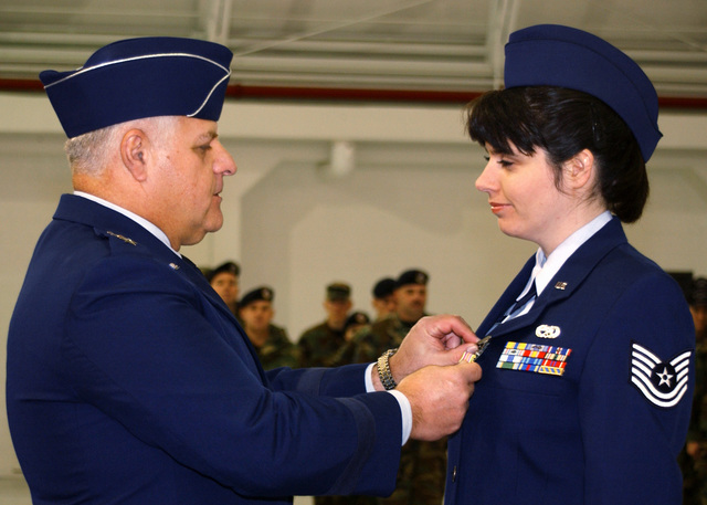 US Air Force (USAF) Technical Sergeant (TSGT) Lynn Decker chosen to represent the Communications Flight, 174th Fighter Wing (FW), receives the Defense of Liberty Medals presented during the December 02 drill in Syracuse, New York (NY), pinned on by Major General Archie J. Berberian, II, New York Air National Guard. The Defense of Liberty Medal, presented only once, created by NY Governor George E. Pataki specifically for those who directly responded to the events of September 11, 2001
