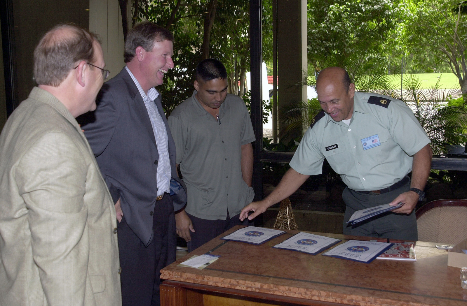 US Army (USA) STAFF Sergeant (SSG) Jorge Esquilin (right), assigned to the US Army South (USARSO) Tactical Exercise Division hands out welcome packets during the Mid-Planning Conference for Peacekeeping Operations South 03 (PKO South 03), held at the Sheraton Hotel, Buenos Aires, Argentina (ARG)