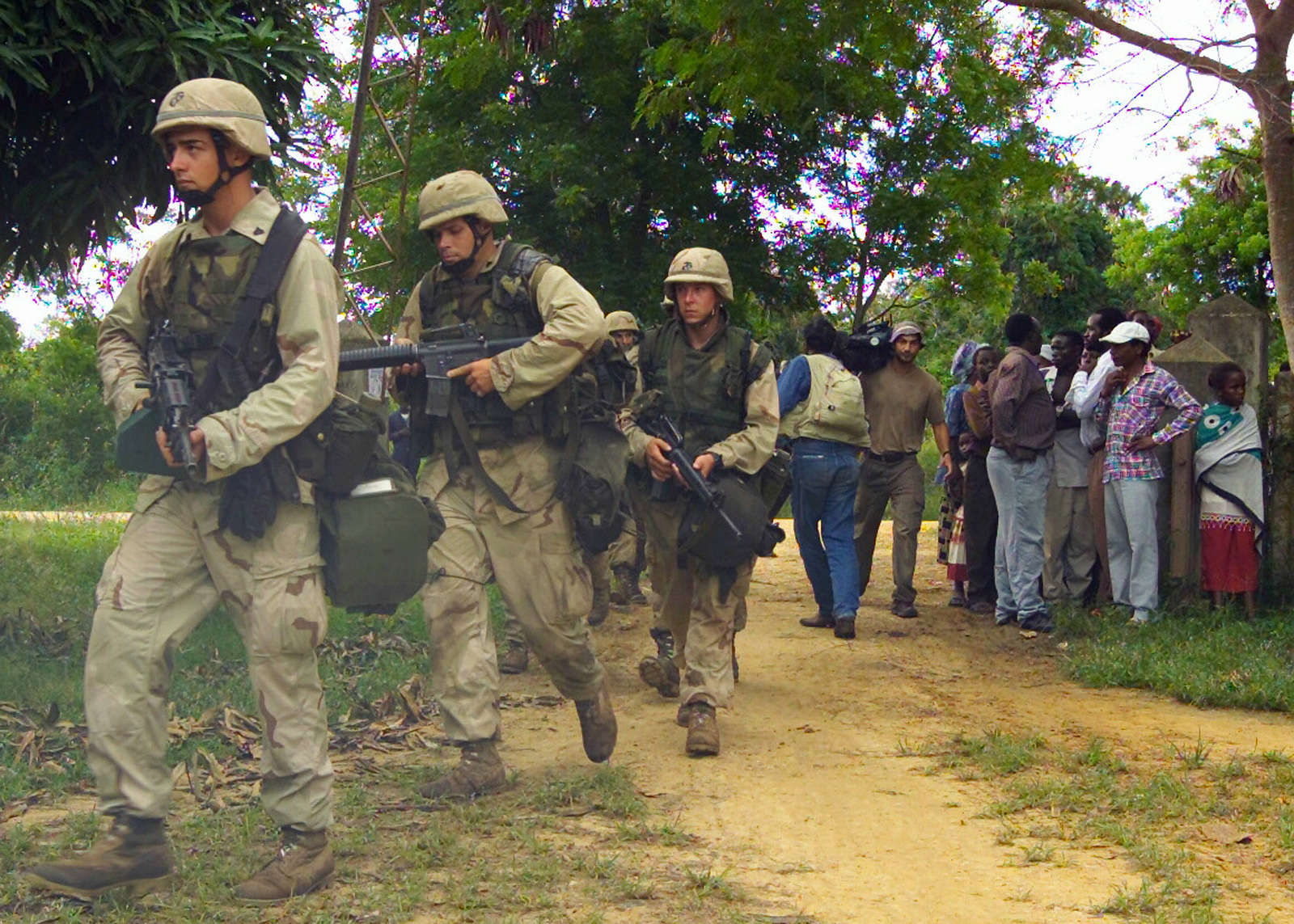 At a local village with the media in trail, Marines from the 24th Marine Expeditionary Unit (Special Operations Capable) (MEU SOC) provide security at a Medical and Dental Civil Affairs Project as part of Exercise EDGED MALLET 2003 in Manda Bay, Kenya