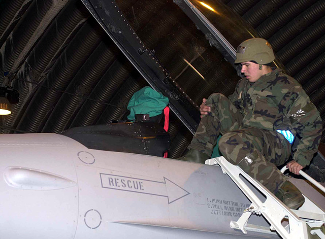 US Air Force (USAF) AIRMAN First Class (A1C) Drew St. Pierre, a Crew CHIEF with the 31st Air Maintenance Squadron (AMS), climbs an F-16 Fighting Falcon fighter cockpit during the local Salty Nation Exercise