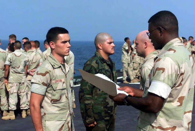 """United States Marine Corps (USMC), Lance Corporal (LCPL) Harry A. Jordan, Automatic Rifleman, with the first platoon, Company """"E"""" Battalion Landing Team, 2nd Battalion, 2nd Marines, 24th Marine Expeditionary Unit (MEU) receives a letter of appreciation from the Navy aboard the USS TORTUGA (LSD-46) Dock Landing ship"""