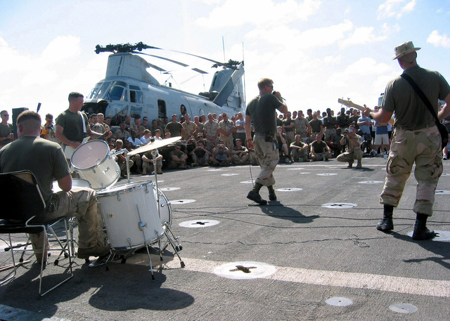 Marines from the 24th Marine Expeditionary Unit (Special Operations Capable) (MEU SOC) perform at a talent show held aboard USS AUSTIN (LPD 4) in the US Central Command Area of Responsibility (CENTCOM AOR). A CH-46 Sea Knight sits in the background