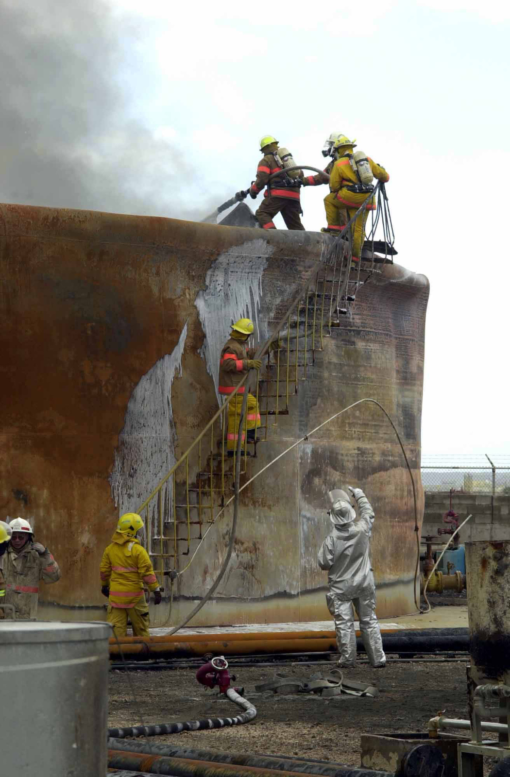 US Air Force (USAF) MASTER Sergeant (MSGT) Kenneth Reeves from the 36th Civil Engineer Squadron (CES), Fire Protection Flight stationed at Andersen Air Force Base (AFB), Guam works with members of the Guam Fire Department to extinguish a fuel tank fire on the Cabras Island tank farm