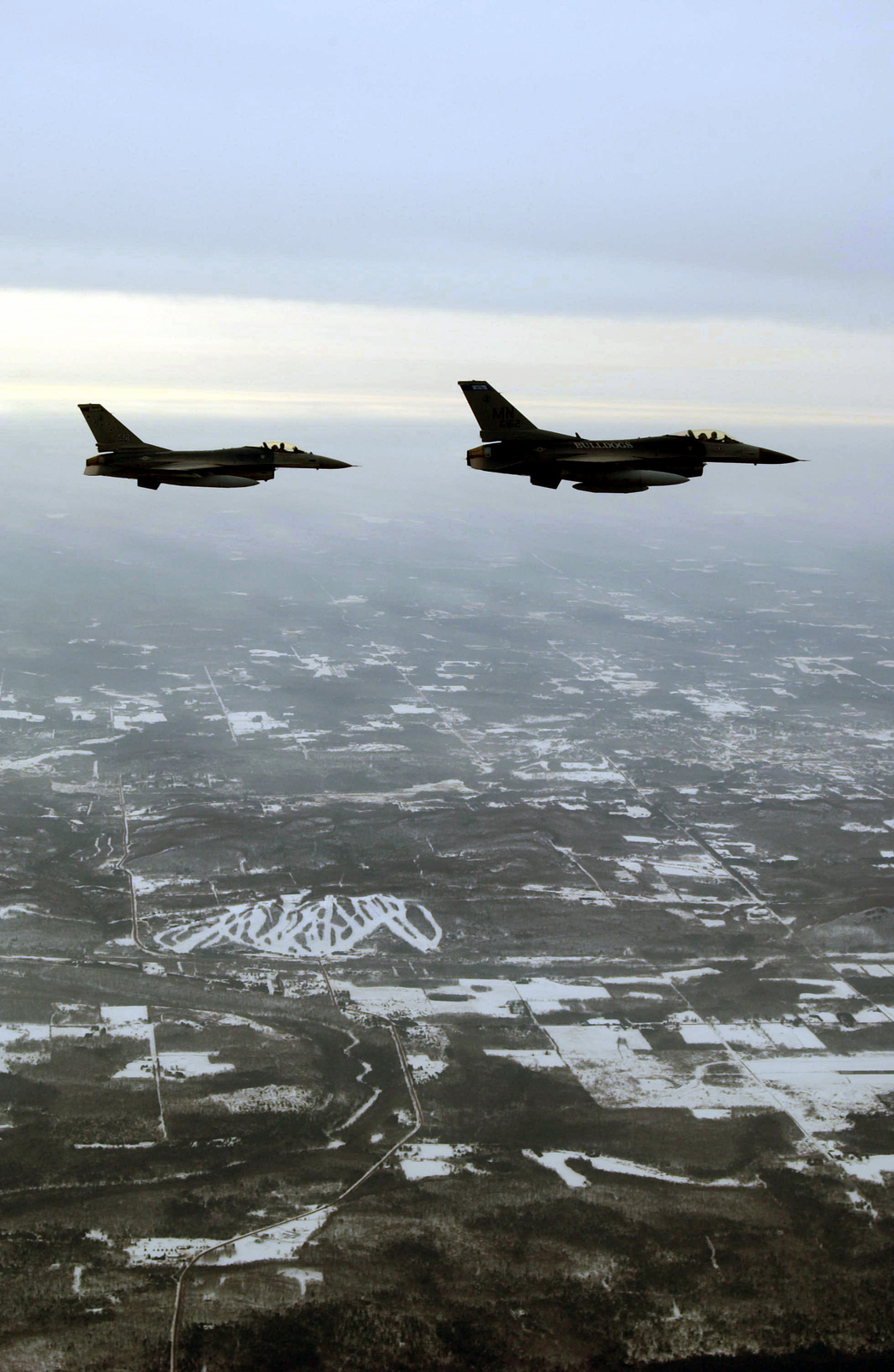A US Air Force (USAF) F-16A Fighting Falcon, 148th Fighter Wing (FW), escorts home the first of many F-16C Fighting Falcons. The F-16C, on the right, is enroute from Syracuse, New York, to the 148th FW, Minnesota Air National Guard Base (ANGB), in Duluth
