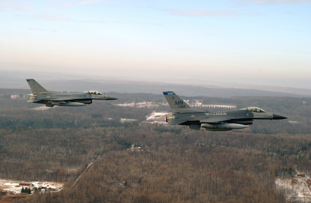 A US Air Force (USAF) F-16A Fighting Falcon, 148th Fighter Wing (FW), Minnesota Air National Guard Base (ANGB), escorts home the first of many USAF F-16C Fighting Falcons, on the right, enroute from Syracuse, New York, to the 148th FW, in Duluth