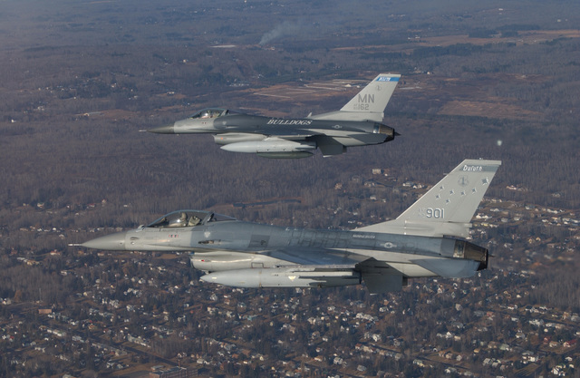 A US Air Force (USAF) F-16A Fighting Falcon, 148th Fighter Wing (FW), Minnesota Air National Guard Base (ANGB), escorts home the first of many USAF F-16C Fighting Falcons, top, enroute from Syracuse, New York, to the 148th FW, in Duluth