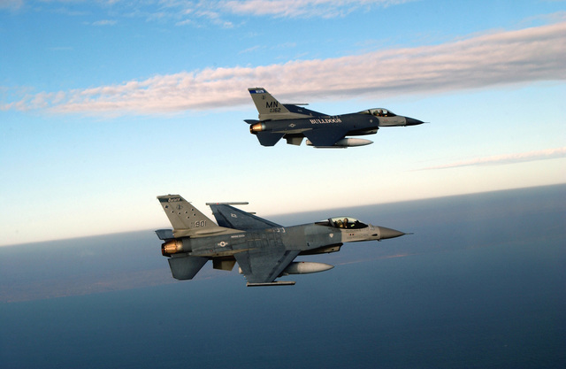 A US Air Force (USAF) F-16A Fighting Falcon, 148th Fighter Wing (FW), Minnesota Air National Guard Base (ANGB), escorts home the first of many USAF F-16C Fighting Falcons, upper right, enroute from Syracuse, New York, to the 148th FW, in Duluth