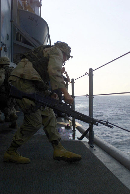 """On the top deck of the USS TORTUGA (LSD-46) Dock Landing ship, United States Marine Corps (USMC), Corporal (CPL) Ryan L. Marshall from Meridian, Texas, a first squad leader with the third platoon, Company """"E"""" Battalion Landing Team, 2nd Battalion, 2nd Marines, 24th Marine Expeditionary Unit (MEU) moves into a gun position with an FNMI 7.62 mm M240 Machine Gun"""