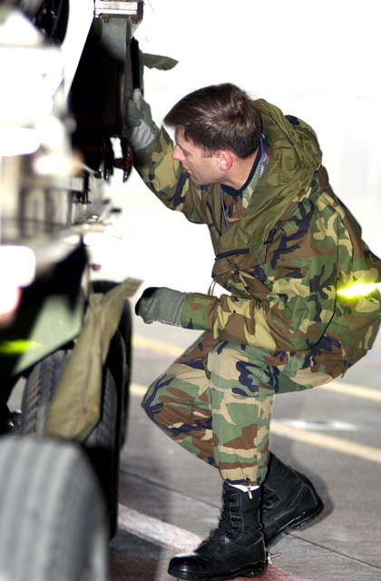 US Air Force (USAF) STAFF Sergeant (SSGT) Chris Harvey, Crewchief, 31st Aircraft Maintenance Squadron (AMS), closely monitors the transfer of a jet engine from the heavy-duty transport trailer to the installation trailer