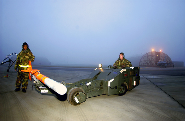 US Air Force (USAF) Weapons Load Team members, AIRMAN First Class (A1C) Brandon Sisk (left), and A1C Thomas Stephens, both Weapon Systems Apprentice, 31st Aircraft Maintenance Squadron (AMS), prepare to load an Acceleration Monitor Assembly (AMA) onto the rail of the F-16 Fighting Falcon prior to launch