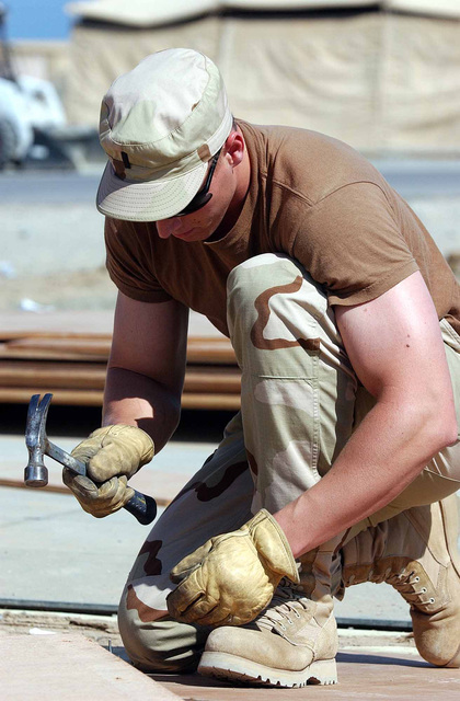 US Air Force (USAF) First Lieutenant (1LT) David Jokinen, an engineering chief assigned to the 321st Expeditionary Civil Engineer Squadron (CES), hammers nails on a temper tent at a forward-deployed location in Southwest Asia, in support of Operation ENDURING FREEDOM