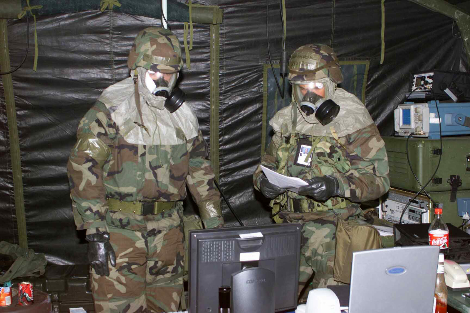 Wearing Mission-Oriented Protective Postures level 4 (MOPP-4) over wear, US Air Force (USAF) AIRMAN First Class (A1C) Mikhail Woltering, left and SENIOR AIRMAN (SRA) Joseph Andrews, right, both satellite communications specialists, with the 52nd Communications Squadron (CS), Spangdahlem Air Base (AB), Germany, carry on with the mission during an alarm, in support of local Exercise Operation Winter Chill 2002