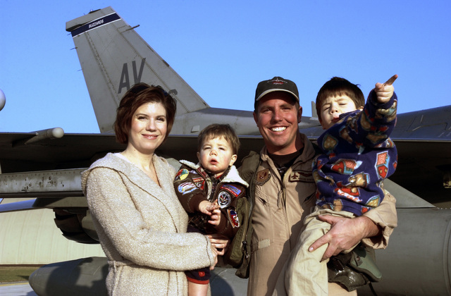In front of his US Air Force (USAF) F-16CG Fighting Falcon, USAF Captain (CAPT) Kevin Dydyk, Pilot, 31st Fighter Wing (FW), poses with his wife and children after returning home from a three-month deployment from Kuwait